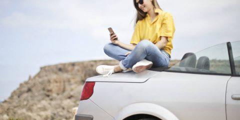 girl-sitting-on-car-using-mobile-phone-app