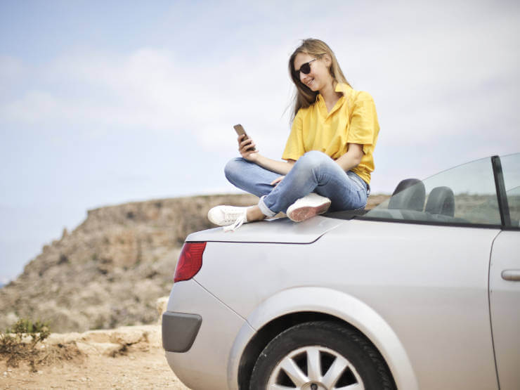 girl-sitting-on-car-using-mobile-phone-app
